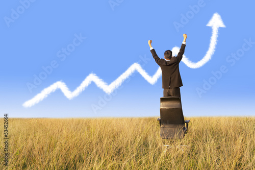 Businessman standing on chair with growing graph cloud
