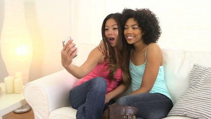 Two happy young women taking pictures with a phone