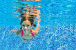 Happy child swims underwater in pool, fun on family vacation - 53454083