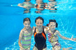 Family swim underwater in pool and having fun on vacation