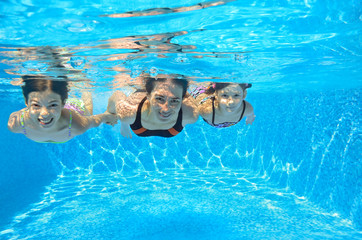 Happy family swim underwater in pool, having fun on vacation
