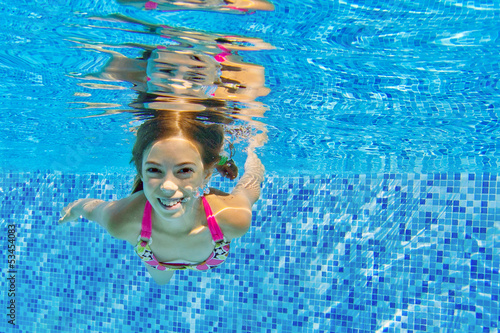 Happy child swims underwater in pool, fun on family vacation