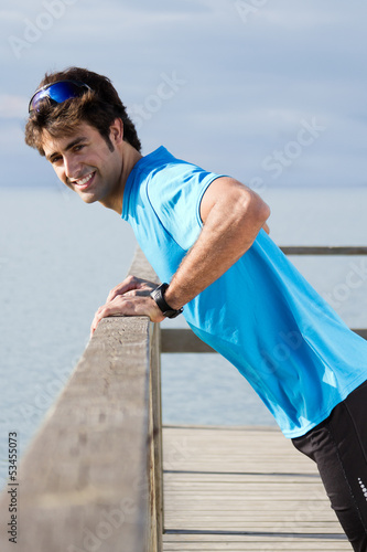 Young man doing push ups near the sea