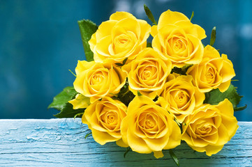 Yellow roses bouquet on the blue background