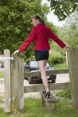 Woman stepping over a stile