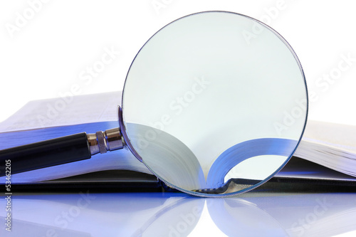 Magnifying glass and open book isolated on white