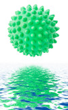 The green sphere with spikes is reflected in water.