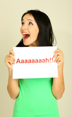 """Surprised young woman holds inscription """"ah"""" on grey background"""