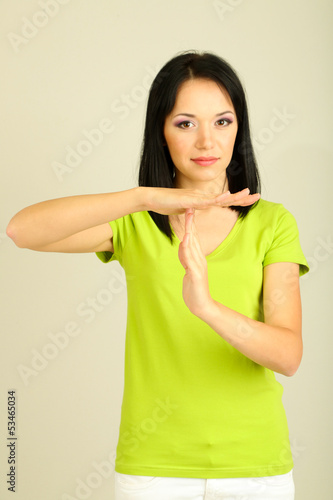 Girl showing time out sign on grey background