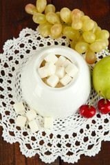 Refined sugar in white sugar bowl on wooden background