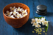 White flowers in a bowl, stones for massage and sea salt. Spa.