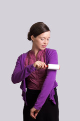 Junge Frau pflegt ihre Kleidung mit einer Fusselrolle