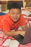 Asian boy working on a laptop computer