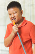 Young asian boy holds a broomstick as a microphone for singing