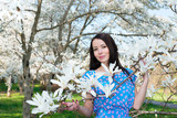 Young woman holding a branch with flowers of Magnolia