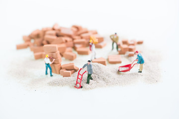 Miniature workmen doing construction work top view close up