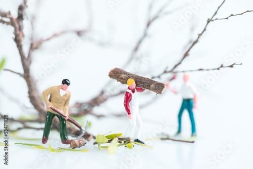 Miniature workmen working together in pruning and cutting trees
