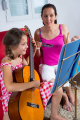 young preteen girl having guitar lesson at home
