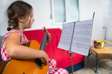 Young girl enjoying playing guitar
