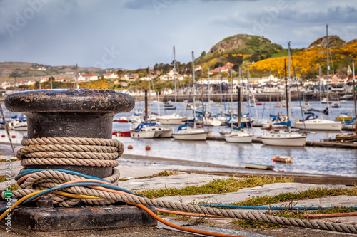 Harbour bollard with mooring ropes and colorful cables