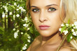 Beautiful blond woman in green forest. flowers