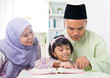 Malay Muslim parents teaching child