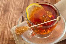 Thé froid avec le cube de glace, citron et le sucre sur la table en bois