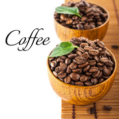 Dark roasted coffee beans in wooden bowl