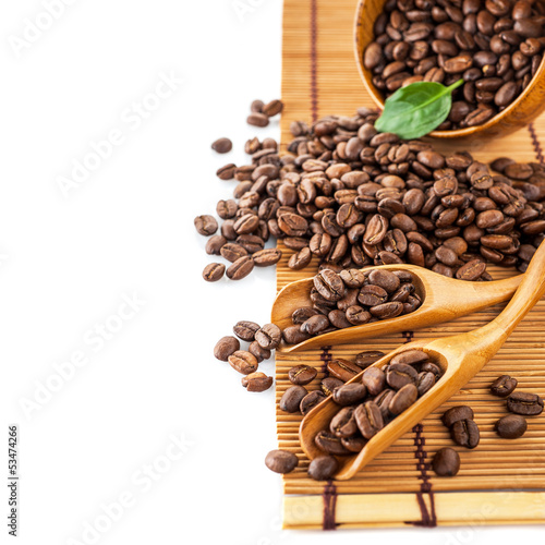 Coffee beans in a wooden scoop on the table
