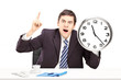 Angry man in an office, holding a clock and pointing with a fing