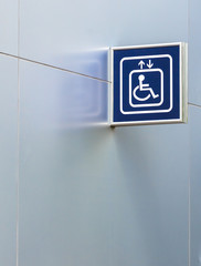 Blue Handicap Elevator Sign on Metallic Wall with Copy space