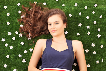 Beautiful young female lying on a grass with daisy flowers