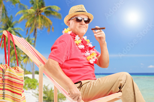 Gentleman smoking a cigar and enjoying on a sun lounger on a bea