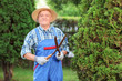 Man trimming a fence in a garden