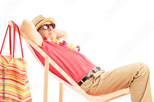 Mature male tourist enjoying on a beach chair