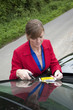 woman removing parking ticket from car windscreen