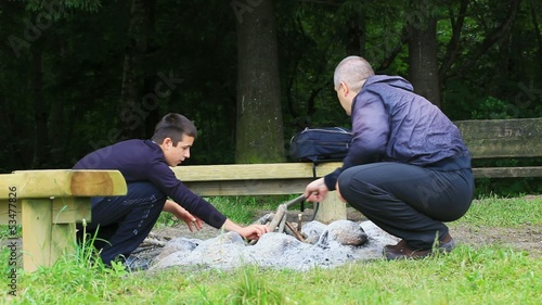 Father and son piling firewood for campfire episode 4