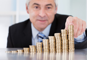 Mature Businessman With Stack Of Coins