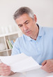Horrified old man reading a letter
