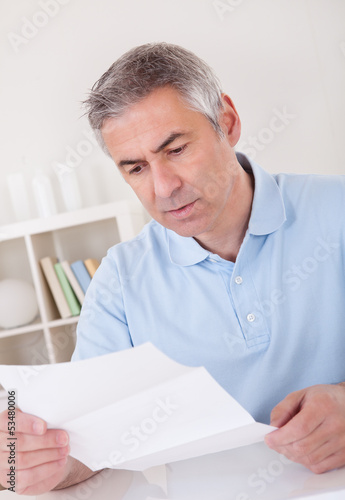 Horrified old man reading a letter