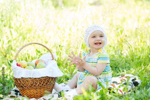 baby eating apples from basket outdoors