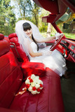 Bride driving convertible car with bouquet of flowers