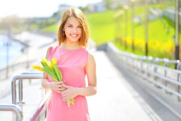 Smiling girl with yellow tulips