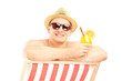 Smiling shirtless guy with cocktail posing on a beach chair