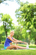 Young athlete woman sitting on a mat and stretching in a park