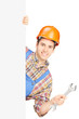 Young manual worker with helmet holding a wrench and posing behi