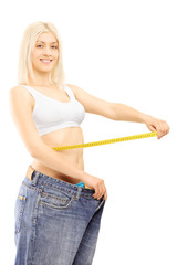Smiling weightloss woman in old pairs of jeans measuring her wai