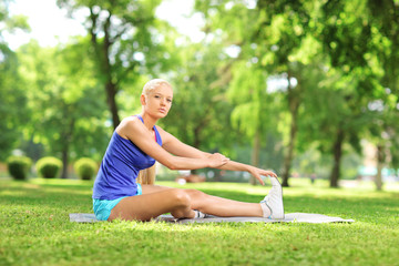 Young active woman sitting on an excercising mat and stretching
