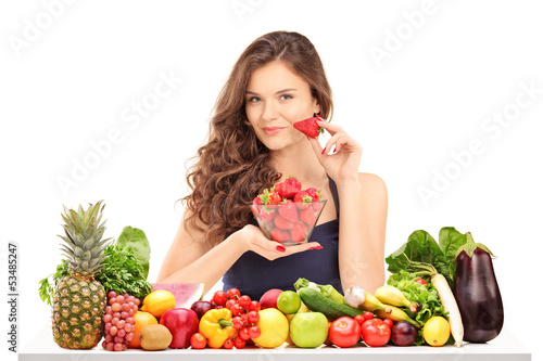 Young female holding a bowl of strawberries and posing behind a