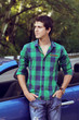 Handsome man with casual clothes posing near his car, outdoors p